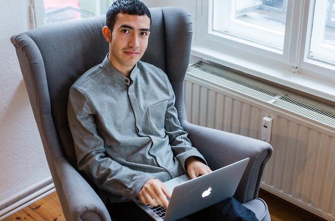 ソファに座りながらパソコンを打つ男性