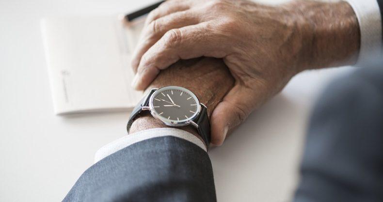 腕時計で時間を確認するビジネスマン