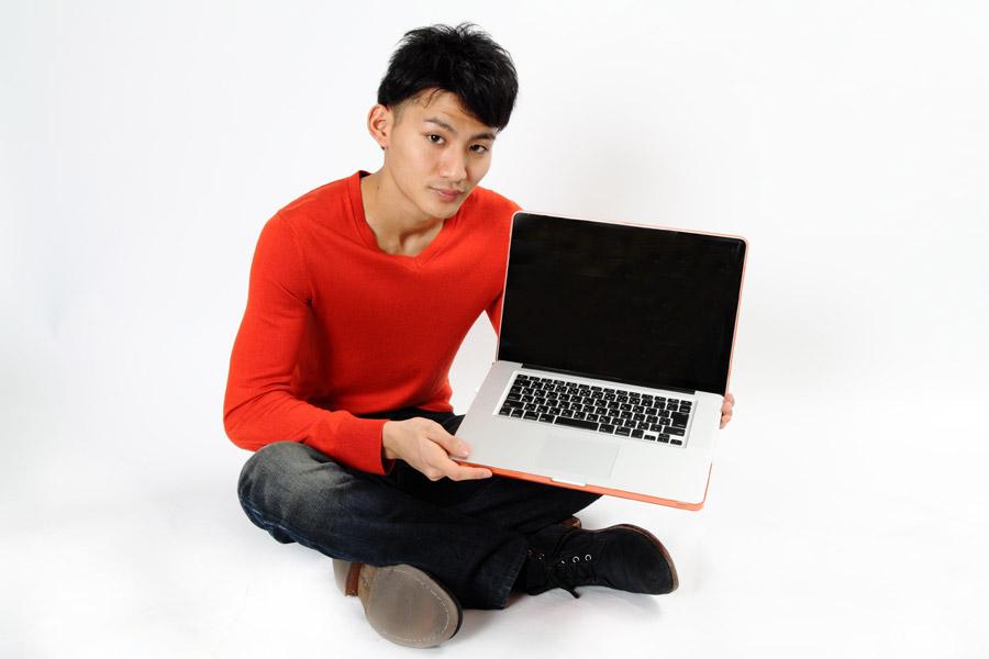 パソコンを手に持つ男性